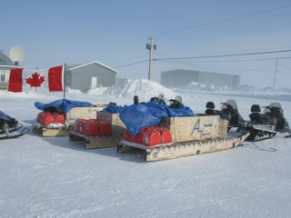 Snowmobiles and sleds (komatiks) with traveling gear used by the Canadian Army Rangers for cold weather patrols.
