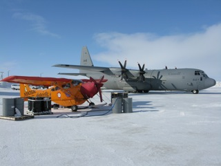 Refueling the Polar Pumpkin from steel barrels immediately adjacent to a Canadian Forces Hercules C-130J.