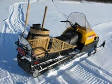 My traveling snowmobile - with snowshoes, scoop shovel, and axe on board.  A rifle and matches - with birch bark fire kindling - are other important survival items.